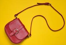 在一条长的皮带的红色皮包在黄色背景 Women& x27; s辅助部件 免版税库存照片