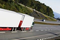 在一条风景高速公路路线的大白色卡车 库存图片