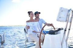 在一条风船的年轻夫妇在日落 库存图片