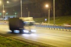 在一条高速公路的卡车夜 免版税库存图片