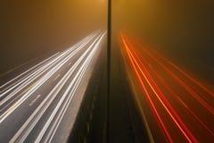 在一条高速公路的夜交通在雾 免版税库存照片