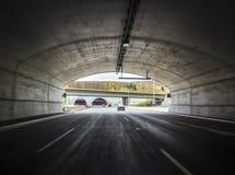 在一条高速公路的宽隧道与移动的汽车 免版税库存照片