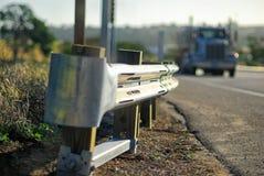 在一条高速公路的栏杆有一大卡车接近的 库存图片