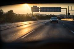在一条高速公路的汽车在日落 免版税库存照片