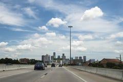 在一条高速公路的汽车有市的地平线的休斯敦在背景中在得克萨斯 免版税库存照片