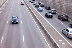 在一条高速公路的汽车通行在城市 库存照片