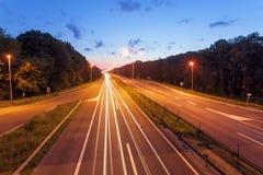 在一条高速公路的长的曝光照片在日落 免版税库存图片