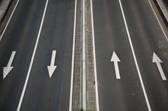 在一条高速公路的细节,有四个箭头的 库存照片