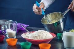在一条黑围裙的厨师酥皮点心在做杯形蛋糕过程中由成份 糖果店烹调的概念 免版税库存图片