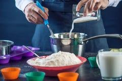 在一条黑围裙的厨师酥皮点心在做杯形蛋糕过程中由成份 糖果店烹调的概念 库存图片