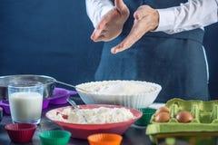 在一条黑围裙的厨师酥皮点心在做杯形蛋糕过程中由成份 糖果店烹调的概念 免版税图库摄影