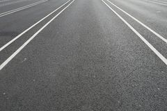 在一条黑沥青街道上的空白线路 免版税库存图片