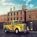 在一条维多利亚女王时代的街道的黄色公共汽车 向量例证