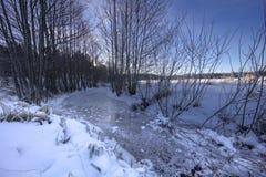 在一条冻小河上的日落,在冬天风景 免版税库存图片