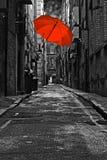 在一条黑暗的小街的红色伞 图库摄影