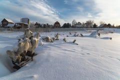 在一条冻河的岸的村庄 免版税库存照片