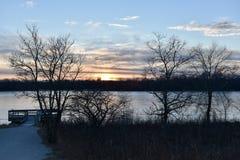 在一条冻河的日落 库存照片