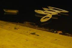 在一条黑水河的黄色小船和河的对角黄色背景支持 免版税图库摄影