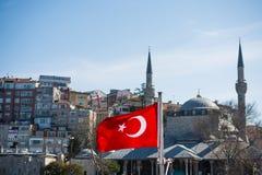 在一条绳索的土耳其国旗吊在有minare的街道 库存图片