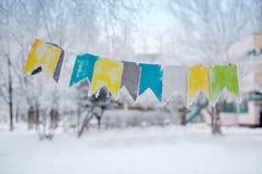 在一条绳索的色的旗子在街道上在冬天 免版税库存照片