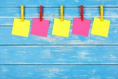 在一条绳索的黄色和红色晒衣夹与五张卡片 免版税库存图片