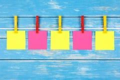 在一条绳索的黄色和红色晒衣夹与五张卡片 库存照片
