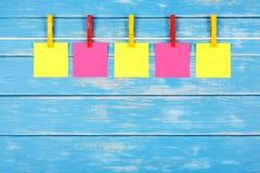 在一条绳索的黄色和红色晒衣夹与五张卡片 图库摄影