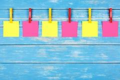 在一条绳索的黄色和红色晒衣夹与六张卡片 库存照片
