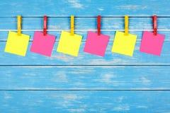 在一条绳索的黄色和红色晒衣夹与六张卡片 免版税库存图片