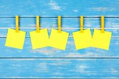 在一条绳索的黄色晒衣夹与五张卡片 免版税库存照片