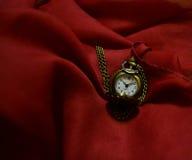 在一条绯红色围巾的口袋手表 库存照片