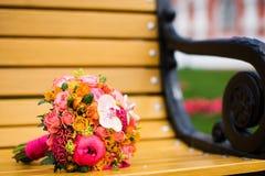 在一条黄色长凳的五颜六色的新娘花束 免版税库存照片