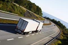 在一条beautyful驾驶的路线的白色卡车 免版税库存照片