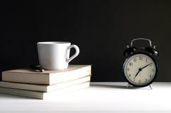 在一杯咖啡的减速火箭的闹钟在上面的旁边书 免版税图库摄影