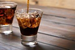 在一杯威士忌酒和可乐倒了可乐 免版税库存照片