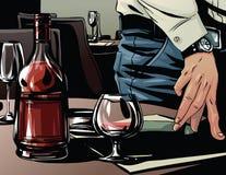 在一杯的典雅的人的手白兰地酒旁边 库存照片