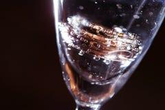 在一杯的婚戒水和气泡 库存图片