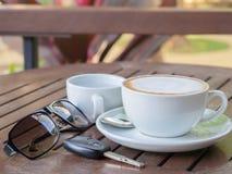 在一杯的热的咖啡拿铁在一张木桌上的白色浆糊,与太阳镜和汽车钥匙 库存照片
