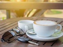 在一杯的热的咖啡拿铁在一张木桌上的白色浆糊,与太阳镜和汽车钥匙 免版税库存图片
