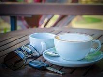 在一杯的热的咖啡拿铁在一张木桌上的白色浆糊,与太阳镜和汽车钥匙 免版税库存照片