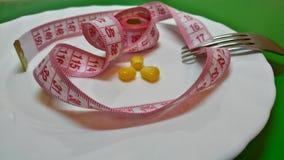 在一板材、叉子和厘米的玉米 免版税库存照片