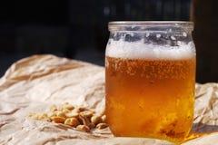 在一枚半公升玻璃瓶子和坚果的新鲜的冰镇啤酒在被弄皱的纸 库存照片
