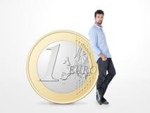 在一枚大一枚欧洲硬币支持的年轻人 库存图片