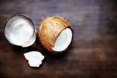 在一枚玻璃和破裂的椰树坚果的椰子水在黑暗的木ba 免版税库存图片