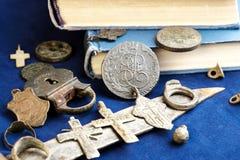 在一枚蓝色布料背景、古老19世纪硬币、一把生锈的刀子和从前居住人的个人项目  库存图片