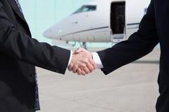 在一架公司喷气机前面的商人握手 免版税图库摄影