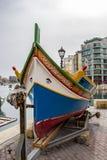在一架小船舷梯的马尔他Luzzu在Spinola海湾,圣朱利安` s,马耳他的岸 免版税库存图片