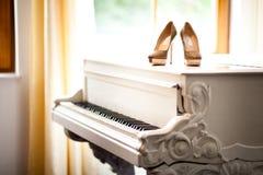 在一架白色钢琴的婚姻的鞋子 免版税库存照片
