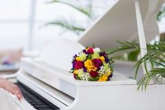 在一架白色钢琴的新娘花束 免版税库存照片
