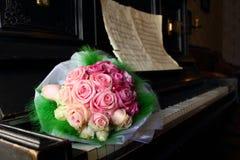 在一架老钢琴的婚礼花束 库存图片